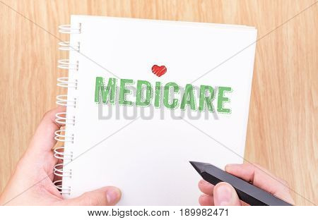 Medicare Word On White Ring Binder Notebook With Hand Holding Pencil On Wood Table,business Concept