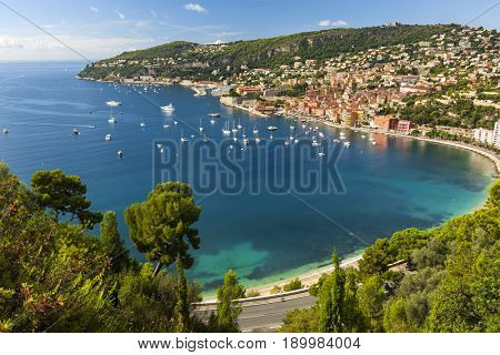 Aerial view of scenic French Riviera mediterranean coast with medieval coastal town Villefranche-sur-Mer, leisure boats anchored in harbor, and road and trees in foreground.