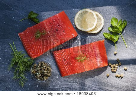 Two pieces of raw wild salmon fish steaks with lemon, capers and herbs, ready to cook, from above.