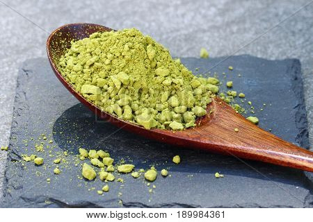 Green Matcha powder in a spoon on a slate colored tile