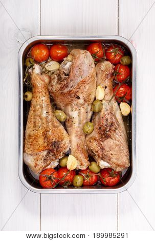 Roasted turkey drumstick with cherry tomatoes green olives and garlic. Grilled turkey legs in cooking pan on white table. Top view.
