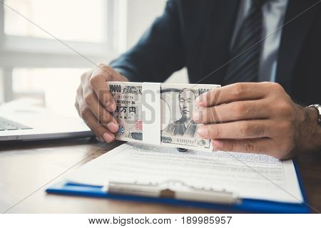 Businessman holding money Japanese yen banknotes on working table