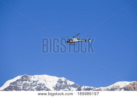 HIMALAYAS ANNAPURNA REGION NEPAL - OCTOBER 16 2016 : Mountain rescue helicopter in Himalaya Mountains on background . Dramatic rescue action in white winter high mountains Nepal.