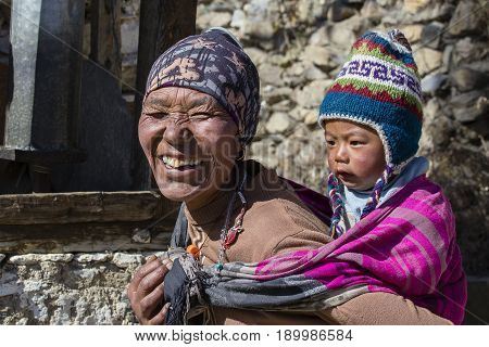HIMALAYAS ANNAPURNA REGION NEPAL - OCTOBER 17 2016 : Portrait nepalese mother and child on the street in Himalayan village Nepal