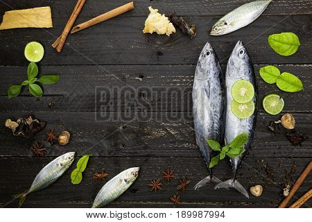 Fresh skipjack tuna fish on dark black background Fish with spices and vegetables cooking background concept