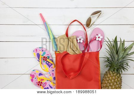 Beach accessory hat sunglasses shoes umbrella and pineapple on white wooden concept summer holiday background and summer sale