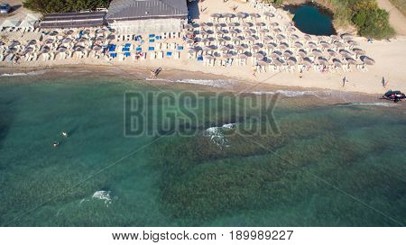 Sea at summer with sandy beach with bathers and parasols