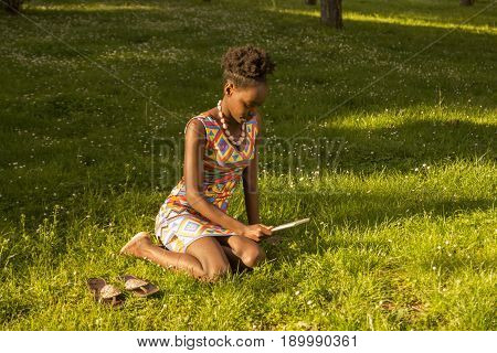 One, Young Adult, Black African American Woman 20-29 Years, Sitting Reading Tablet, Outdoors Park Gr