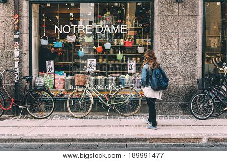 Copenhagen Denmark - August 10 2016. Young woman looking at store window of Notre Dame shopping in Copenhagen with bicycles parked. It offers Nordic design in kitchenware textiles and practical storage solutions.