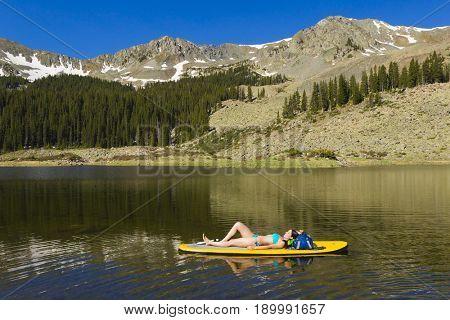 Hispanic woman laying on paddle board