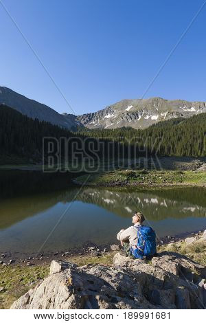Caucasian hiker sitting on boulder