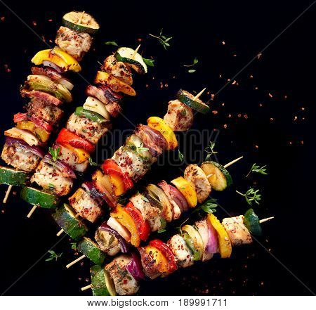 Grilled meat and vegetable skewers with fresh herbs and spices, top view