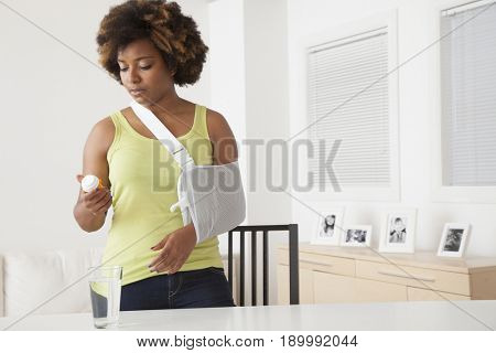 African American woman in sling taking medication