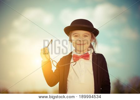 Funny little girl in bow tie and bowler hat holding glasses. Retro stile.