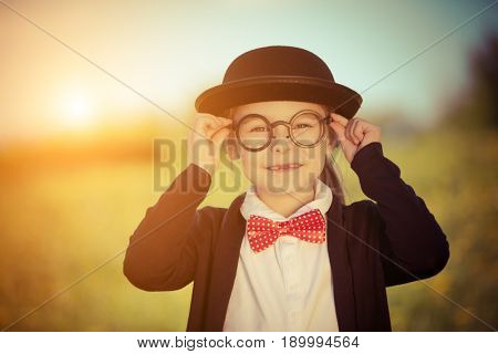 Funny little girl in glasses, bow tie and bowler hat. Retro stile.