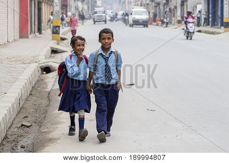 KATHMANDU NEPAL - SEPTEMBER 29 2016 : Young boy and girl going home from school after lessons at the local school in Kathmandu Nepal