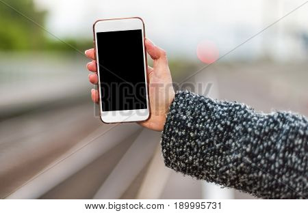 A Woman's Hand Holds An Iphone On The Background Of A Railway