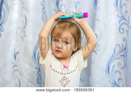 The little girl combs hair a hairbrush