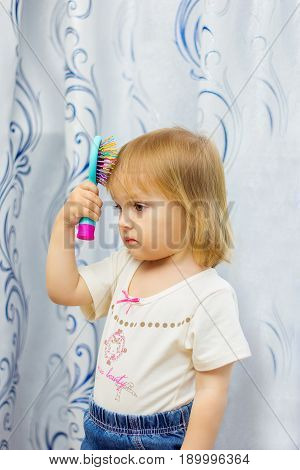 The little girl brushes the hair with a hairbrush