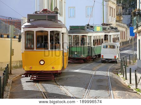 Traditional trams in the narrow streets of Lisbon in the district of Alfama Portugal
