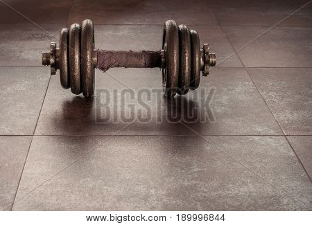 Dumbbell old laying on the ground.It is old because it is used for a long time.