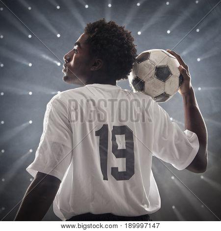 Black soccer player holding ball