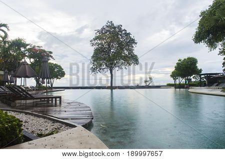 Baan Sansuk Condo Hua Hin Thailand- May 27 2017 : Back view of the Baan Sansuk condo in a rainy day morning where theirs a big swimming poolmany chairs to hang on and to relax in Hua Hin Thailand.