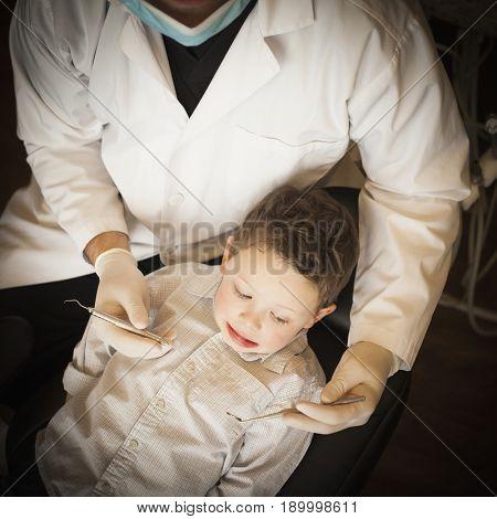 Caucasian dentist examining boy's teeth in office