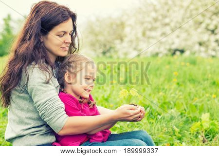 Mother and daughter holding little green plant in hands. Ecology concept