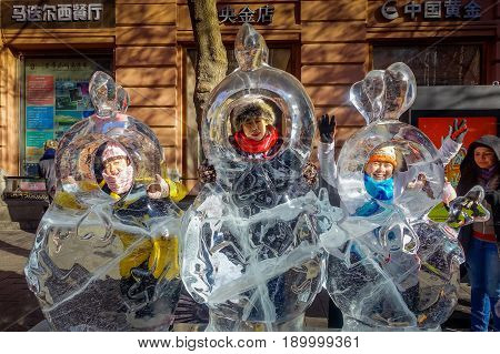 Harbin, China - February 9, 2017: Unknown tourists visiting the ice sculptures in Zhongyang pedestrian street, central street is a commercial long corridor of European architectural art