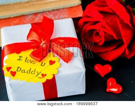 Father's day concept. I LOVE YOU DADY message with red rose two red heart and gift on pink background