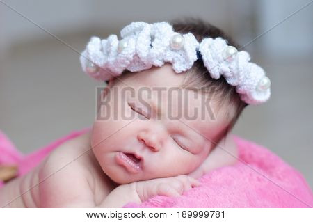 infant sleeping in basket with accessory - head band baby girl lying on pink blanket cute child newborn announcement
