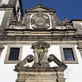 The facade of the parish church of Sao Joao Baptista combines the Mannerist and Baroque styles and a prominence of the Baptism of Christ in Ponte da Barca Portugal poster