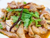 Slide grilled pork salad or Nam Tok garnish with mint leaves and dried chili. Nam Tok is spicy Northeast food of Thai flavors. poster