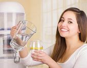 Beautiful smiling woman holding a glass of water in one hand and a pitcher of water in her other hand, with a filter system of water purifier on a kitchen background. poster