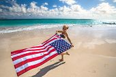 Enjoying woman celebrate independence day waving American flag in tropical Hawaiian beach. Lanikai Beach, east shore of Oahu in Hawaii, USA. Freedom and patriotic concept. Indipendence day. poster