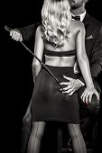Man in tux with whip grab woman lover ass by hand black and white selective coloring isolated poster