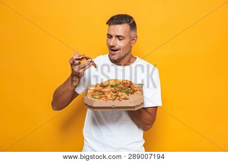 Image of unshaved man 30s in white t-shirt holding and eating pizza while standing isolated over yellow background