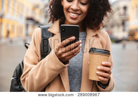 Cheerful young african woman wearing coat walking outdoors, holding takeaway coffee cup, using mobile phone