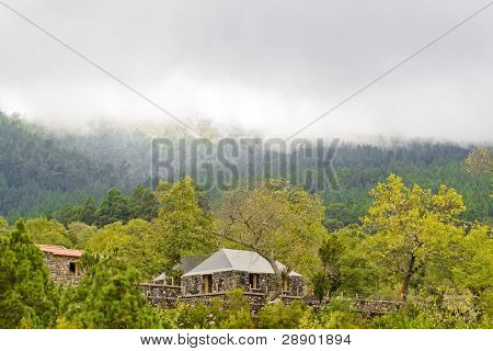 Rustic house in the middle of the forest, near the clouds limit.