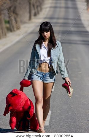 Young woman in the middle of the road with her teddy bear.