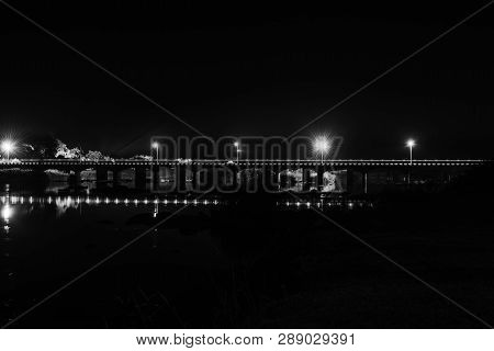 A Night View, With Reflections, Of The Road Bridge Over The Orange River At Upington, A Town In The