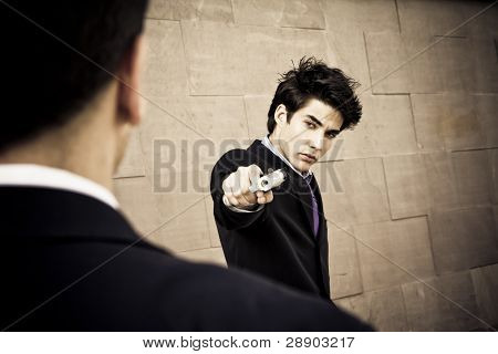 Well dressed man aiming to another with a gun