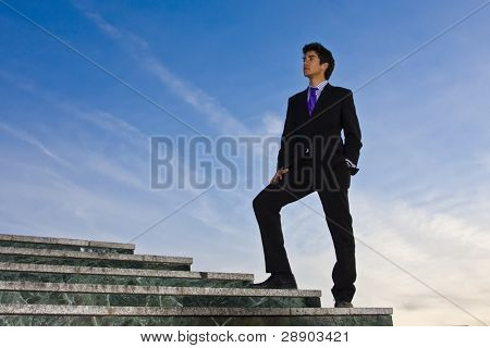 Businessman posing on stairs against blue sky.
