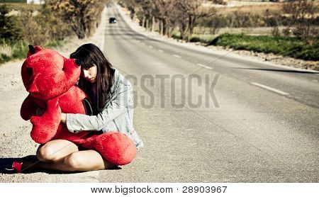 Young girl left behind with her teddy bear.
