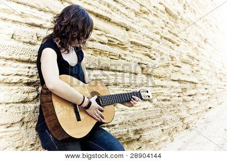 Street artist playin guitar on the wall