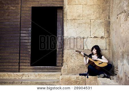 Lone street artist near old iron door.