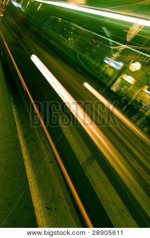 Blurred bus through zebra crossing, green toned.