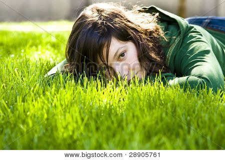 Young woman staring at camera in the grass.