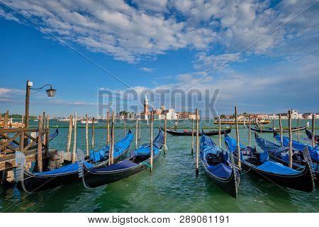 VENICE, ITALY - JUNE 27, 2018: Gondolas and gondolier in lagoon of Venice by Saint Mark (San Marco) square with San Giorgio di Maggiore church in background in Venice, Italy